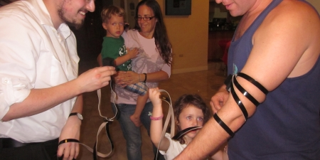 Daddy putting on tefillin is a family experience.