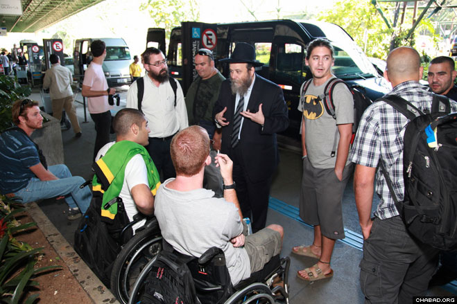 Chabad-Lubavitch Rabbi Noach Gansburg of the local New Horizon Center meets a group of injured Israeli soldiers touring Brazil at the airport in Rio de Janeiro.