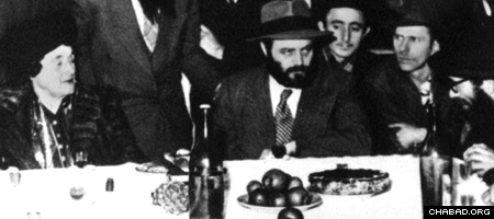 Rebbetzin Chana Schneerson sits beside her son and the future Rebbe, Rabbi Menachem M. Schneerson, of righteous memory, at a Chasidic gathering in Paris where he went to care for her and bring her to the United States. (Photo: Lubavitch Archives)