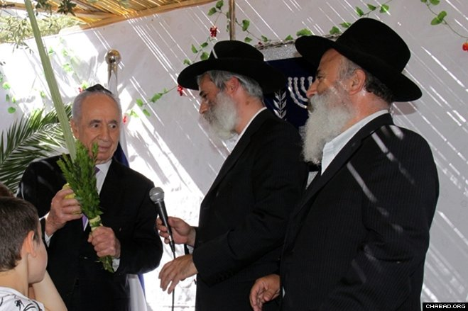 Kfar Chabad Mayor Rabbi Yami Lifshitz gave Israeli President Shimon Peres a set of the Four Species to make a special blessing in the presidential sukkah in Jerusalem. (Photo: Yosef Avi Yair Angel)