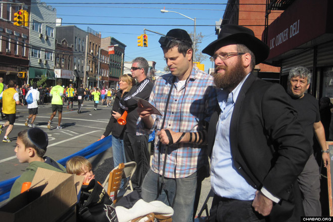 Chabad-Lubavitch of Long Island City director Rabbi Zev Wineberg helps a Jewish spectator don the prayer boxes known as tefillin during Sunday's annual New York City Marathon.