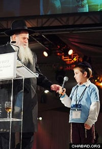 A son of Chabad-Lubavitch emissaries announces a country during the signature roll call of Chabad-Lubavitch emissaries.