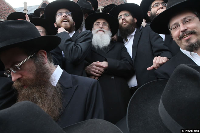 Rabbi Dovid Teichtel of Israel, center, waits with other Chabad-Lubavitch emissaries to have a group picture taken in front of Chabad-Lubavitch world headquarters in the Crown Heights section of Brooklyn, N.Y.