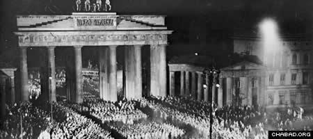 Thousands of uniformed men and women swarm through the Brandenburg Gate after Hitler's formal rise to power on Jan. 30, 1933. (Photo: Heinrich Hoffmann/Bundesarchiv Federal Archive)