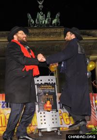 Chabad-Lubavitch Rabbis Yehuda Tiechtel, left, and Shmuel Segal dance in front of the Brandenburg Gate. (Photo: Avraham Golovacheov)