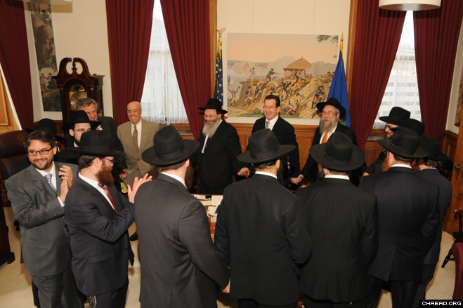 A delegation of rabbis representing the 23 Chabad-Lubavitch centers throughout Connecticut danced with Gov. Dannel P. Malloy during a Chanukah celebration in his capitol office.