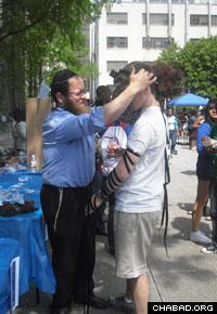 Rabbi Zalman Lipskier helps a Jewish student don the prayer boxes known as tefillin.