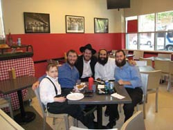 Mendel enjoying a meal in Brooklyn with some old and new friends from Pesti Jesiva and Chabad.org. (L-R) Mendel, Rabbis Yudi Dukes, Moishy Goldman, Menachem Posner, and Chaim Benjaminson.