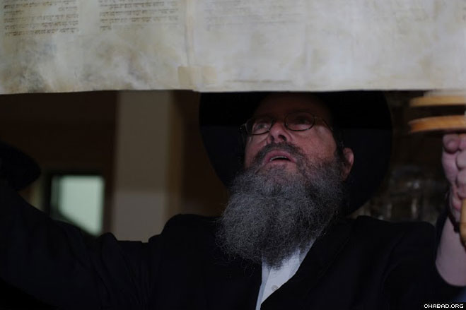 Chabad House of Antwerp director Rabbi Shabtai Slavaticki holds up a Torah scroll saved from the Holocaust for members of the Jewish community of Krefeld, Germany, to see. Slavaticki brought the scroll back from Belgium after an extensive repair presided over by ritual scribe Rabbi Shuki Lipschitz.