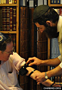 Rabbi Osher Litzman helps a Jewish man don the prayer boxes known as tefillin in Seoul.