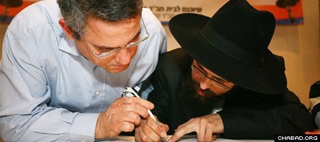 A supporter of the Jewish community in South Korea writes one of the first letters in a Torah scroll commissioned by the Chabad House in Seoul during a 2008 launch party in Israel.