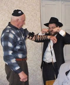Margolin putting on tefillin with a Gaisin Jew a few hours before Pesach.