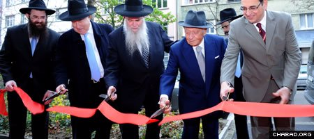 Rabbi Zalmen Wishedski, Gabriel Feldinger, Rabbi Moshe Kotlarsky, philanthropist Sami Rohr, and interim Israeli Ambassador Shalom Cohen cut the ceremonial ribbon outside the new Feldinger Chabad Jewish Center in Basel, Switzerland. (Photo: Meir Dahan)