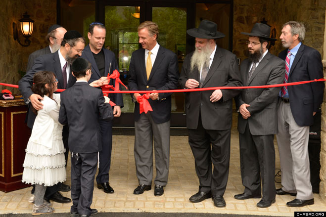 Rabbi Yitzchok Tiechtel helps his children Levi and Chana present the ceremonial ribbon cutting scissors to Tennessee Gov. Bill Haslam, who joined Rabbi Moshe Kotlarsky, vice chairman of Merkos L'Inyonei Chinuch, the education arm of Chabad-Lubavitch, for the grand opening of the Genesis Campus for Jewish Life.