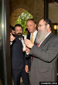 Rabbi Shlomo Tiechtel, father of Rabbi Yitzchok Tiechtel, affixes a mezuzah to the entryway of the new center in Nashville.
