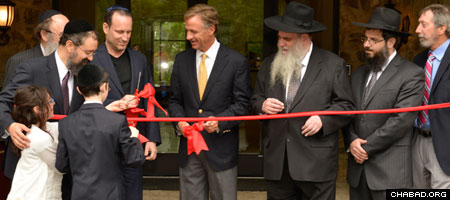 Rabbi Yitzchok Tiechtel helps his children Levi and Chana present the ceremonial ribbon cutting scissors to Tennessee Gov. Bill Haslam, who joined Rabbi Moshe Kotlarsky, vice chairman o Merkos L'Inyonei Chinuch, the education arm of Chabad-Lubavitch, for the grand opening of the Genesis Campus for Jewish Life.