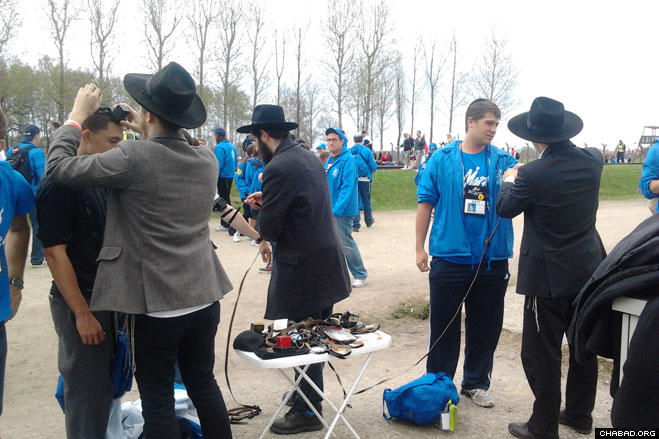 Chabad-Lubavitch rabbinical students from yeshivas throughout Israel help participants in the March of the Living don the prayer boxes known as tefillin.