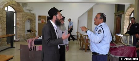 Rabbi Gavriel Marzel speaks with police after the discovery of six Torah scrolls stolen from his Tzemach Tzedek Synagogue in the Old City of Safed, Israel.