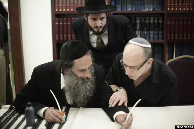 Rabbi Moshe Kievman, director of the Highland Lakes Jewish Center-Chabad Chayil, looks on as a community member writes a letter in a new Torah scroll with the help of a ritual scribe.