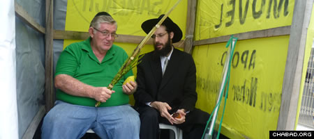 Chabad-Lubavitch Rabbi Arieh Raichman helps a local Jew make a blessing on a lulav and etrog inside of a mobile sukkah in Manaus, Brazil.