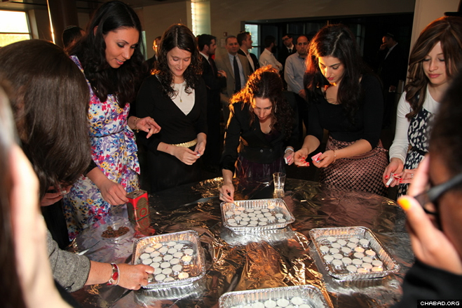 Jewish women light candles to usher in the Sabbath May 18 at a young professionals Shabbaton organized by the Tzach Lubavitch Youth Organization in Crown Heights.
