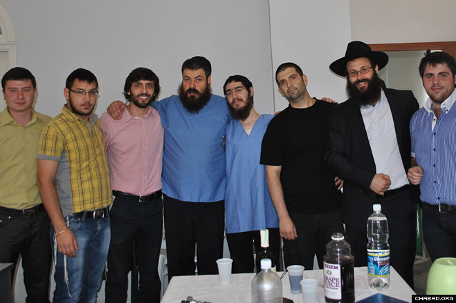 Rabbi Chaim Danzinger and 26-year-old Rostov resident Yura, second and third from right, pose with friends and a ritual circumciser at the young man's circumcision celebration. Yura took the Hebrew name Adam at the event.