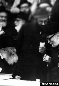 Rabbi Yosef Wineberg, right, speaks with the Rebbe, Rabbi Menachem M. Schneerson, of righteous memory, at a public Chasidic gathering.