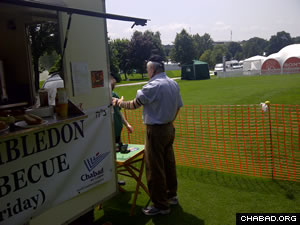 A Wimbledon spectator takes a prayer break alongside a kosher food truck operated by the local Chabad House.