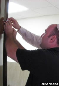 A Jewish businessman affixes a mezuzah to his workplace entryway with the assistance of Rabbi Moshe Greenwald.