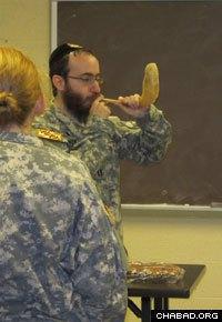Rabbi Chesky Tenenbaum blows a ram's horn known as a shofar.