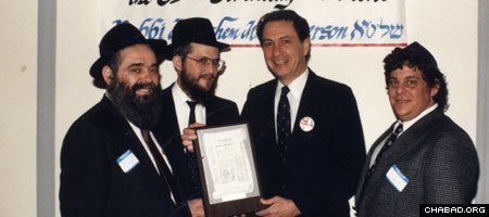 Rabbis Zalman Lipsker of Philadelphia and Yisroel Rosenfeld of Pittsburgh, Pa., present a plaque to Sen. Arlen Specter at the 1987 celebration of Education Day, USA, and the commemoration of the 85th birthday of the Rebbe, Rabbi Menachem M. Schneerson, of righteous memory. (Photo: Lubavitch Archives)
