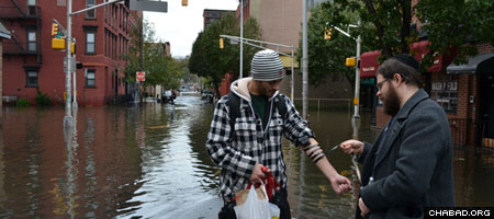 Rabbi Moshe Schapiro from Hoboken, N.J., helps a Jewish victim of Hurricane Sandy don the prayer boxes known as tefillin.