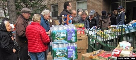 """מתנדבים עוזרים בחלוקת מזון ומים המאורגנת על ידי בית חב""""ד."""