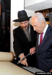 Israeli President Shimon Peres inspects an interactive computerized Torah scroll at the museum.