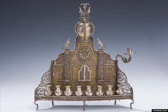 """A LARGE AND IMPORTANT BAAL SHEM TOV STYLE CHANUKAH LAMP. Ukraine, c. 1820. In spectacular form and condition. Marked with crossed swords and 12 marks. With bird finial. 12.2"""" tall."""