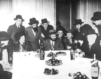 Paris, 1947. Após a reunião de Rebetsin Chana com seu filho mais velho, uma recepção especial foi preparada com a participacão de chassidim e amigos. Aqui, o futuro Rebe preside um farbrenguen, com a mãe sentada à sua direita.
