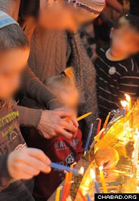 A recent widow and her children light the Menorah, surrounded by new friends.