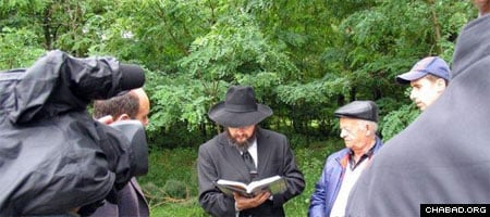 Rabbi Alexandar Faingold and local Jewish residents at the burial of Jewish bones found at a building site in Nytshin, Ukraine.