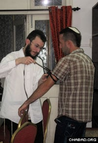 The rabbi says that soon they will restart weekly Jewish classes and yeshiva learning programs on Sundays for the local youth. Here he helps a local resident put on tefillin.