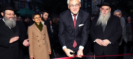 Flanked by Rabbi Shabtai Slavaticki (left) and Rabbi Moshe Kotlarsky, Kris Peeters, the Flemish Minister-President, cuts the ribbon to the new Chabad Center in Antwerp. (Photo: Donald Woodrow)