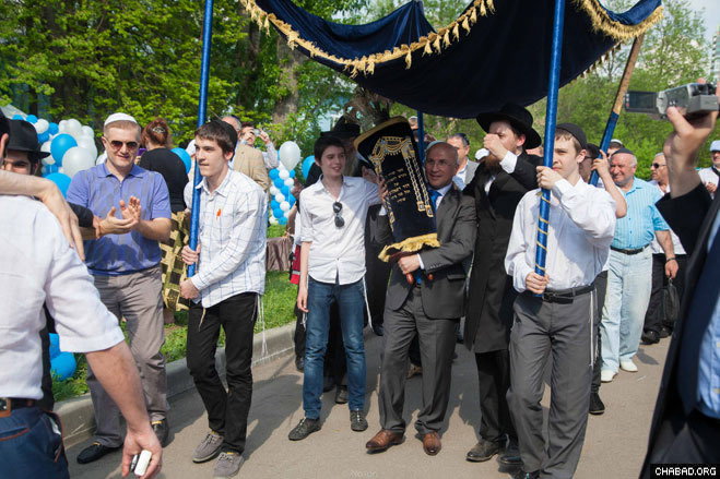 Local residents and guests dance in the streets of Moscow with their new Torah scroll.