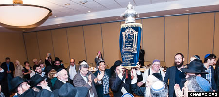 Dancing with the Torah scroll following the penning of its final letters. (Photo: Leon Shkolnik)