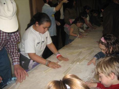 Krystal Schucart, left, rolls her own Passover matzo.JPG