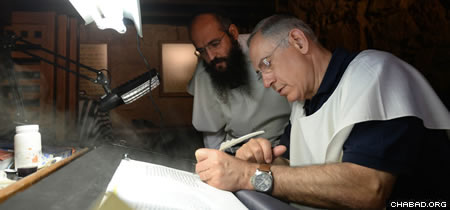 Israeli Prime Minister Benjamin Netanyahu writes a word in a Torah scroll at the synagogue in Masada as Rabbi Shimon Elharar looks on.