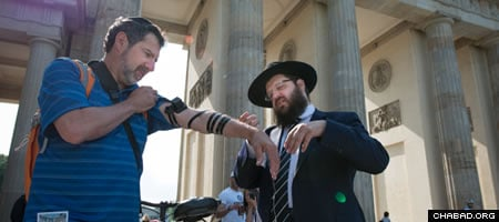 Lester on the first day of his European tour putting on tefillin with the help of Rabbi Yehuda Tiechtel. (Photo: Clifford Lester)
