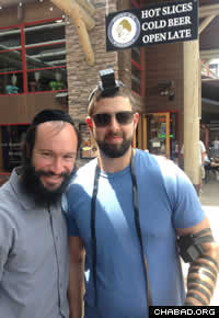 """I stand every Thursday outside of a friend's store in the Town Square with tefillin and Shabbos candles and offer passersby a mitzvah on the go,"" says Mendelsohn. ""This photo is of Ben from San Francisco who was putting on tefillin for the first time in his life. He mentioned that he was recently at the Kotel (Western Wall) in Jerusalem and because his group was in a hurry, he didn't put on tefillin there and felt bad at his missed opportunity. We made up for it by a different wall, the one outside a store called Moose on the Loose, owned by an Israeli."""