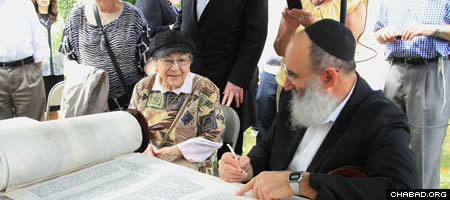 Congregants, family members and well-wishers took turns sitting next to scribe Rabbi Yochanan Nathan as he inscribed the closing verses of Marge Fettman's Torah scroll with a quill pen and special kosher ink.