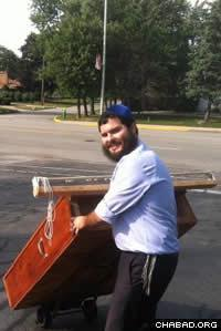 Rabbi Eliezer Zalmanov of Munster, Ind., transporting a specially constructed holy ark from the cozy sanctuary in his home to the Center for Visual and Performing Arts.