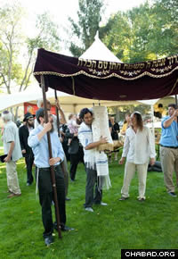 Community members dance with the Torah scroll at the dedication festiviities.