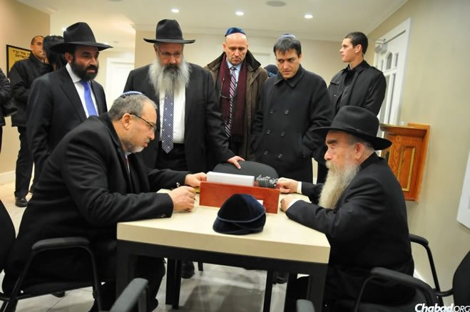 Rabbi Abraham Shemtov, right, chairman of Agudas Chassidei Chabad, advises Israeli foreign minister Avigdor Lieberman on the customs related to the preparation of a petition to the placed at the Rebbe's resting place. Rabbi Shalom Duchman, center, director of Colel Chabad, and Rabbi Levi Edri, left, a close friend of the foreign minister, look on.